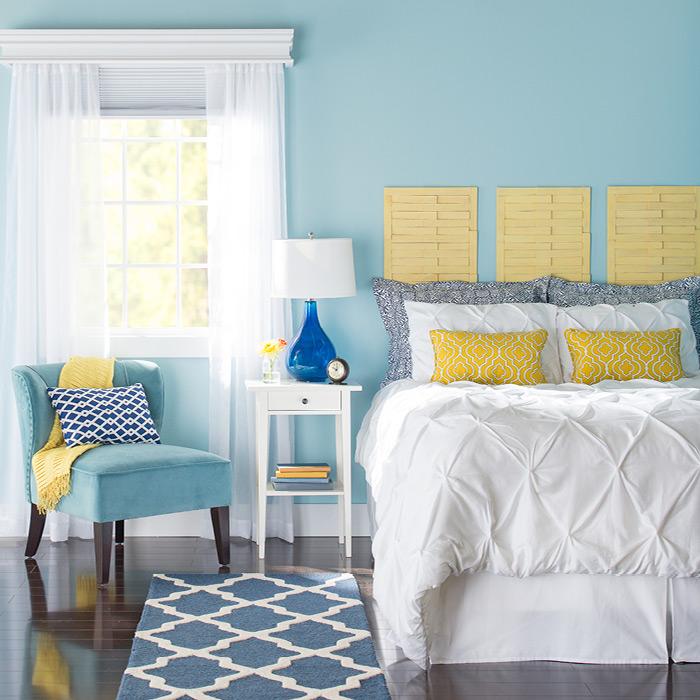 runner rugs beside bed bedroom with blue walls. MBGVJTL
