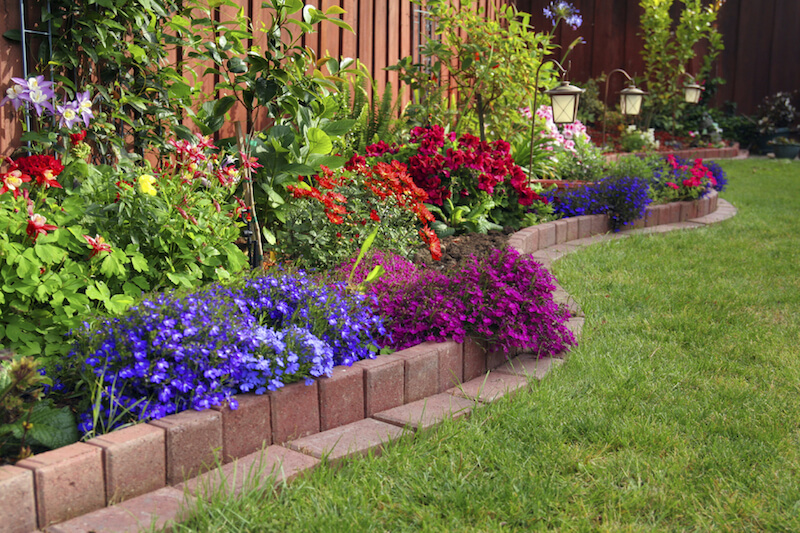 flower bed ideas here is a brick lined flowerbed against a fence in this yard. placing a  flower GZZQIQI